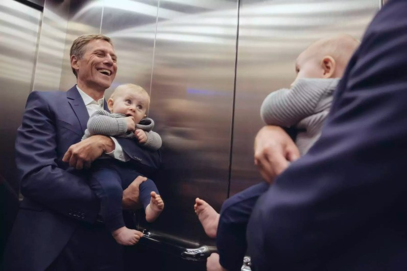 Happy mature businessman holding baby boy looking in mirror in elevator
