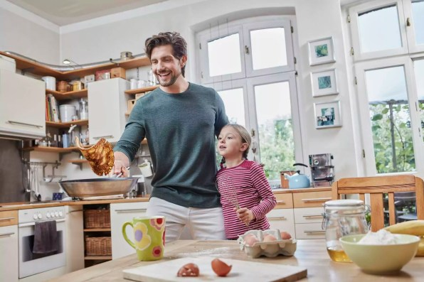 Happy father and daughter baking pancakes in kitchen at home together
