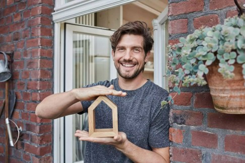 Portrait of smiling man at house entrance holding house model