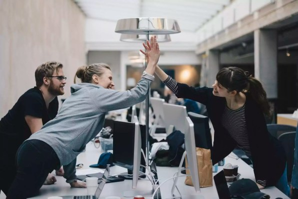 Happy female computer programmers giving high-five over desk in office