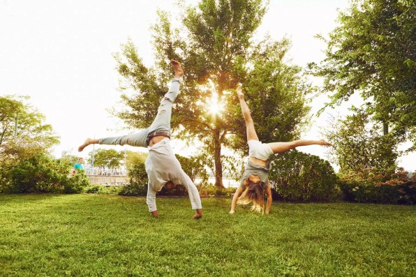Male and female adult friends doing cartwheels in park