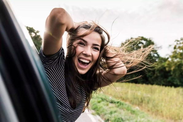Carefree young woman leaning out of car window