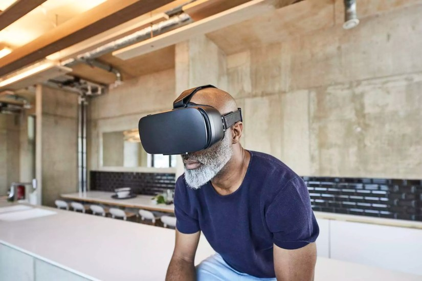 Mature businessman in modern office wearing VR glasses