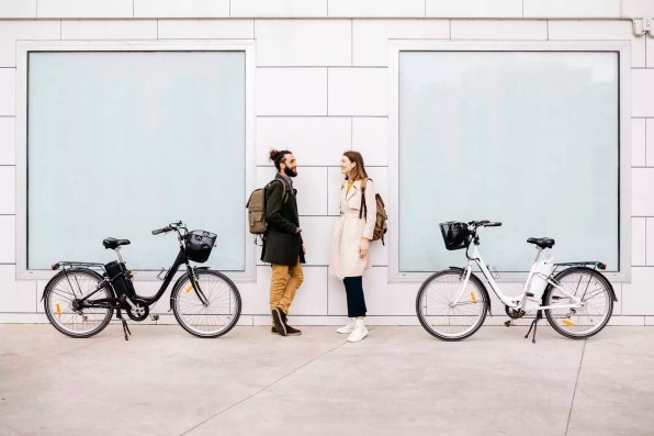 Man and woman with e-bikes standing at a building talking