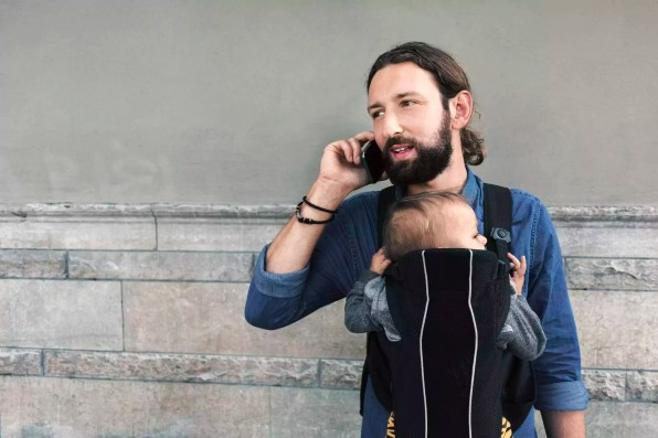 Mid adult man using mobile phone while carrying son in baby carrier against wall