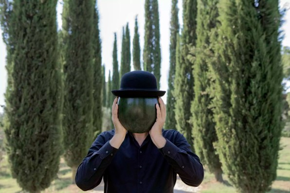 Italy, Tuscany, man surrounded by cypresses wearing a bowler hat holding a melon