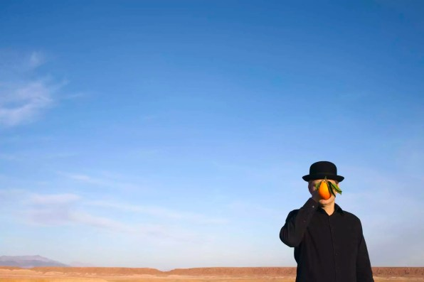 Morocco, Ounila Valley, man wearing a bowler hat holding an orange in front of his face