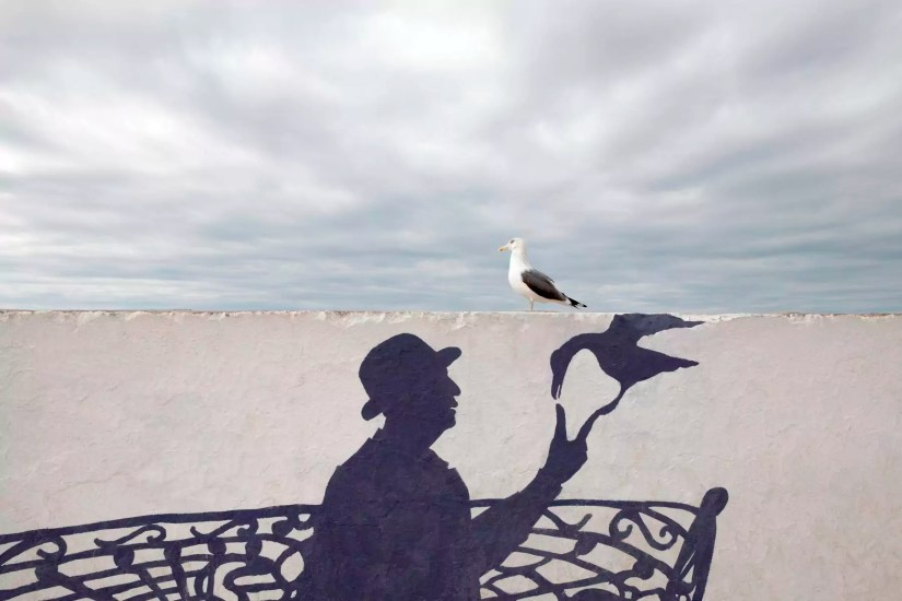 Morocco, Essaouira, wall painting of man wearing a bowler hat with seagull