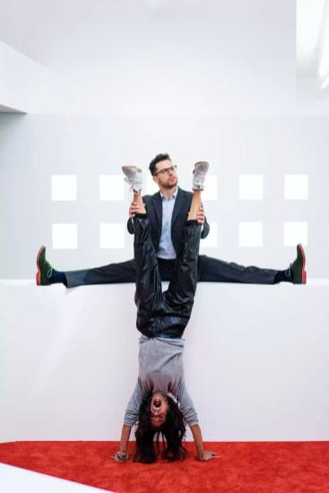 Businessman in office holding woman's legs doing a handstand