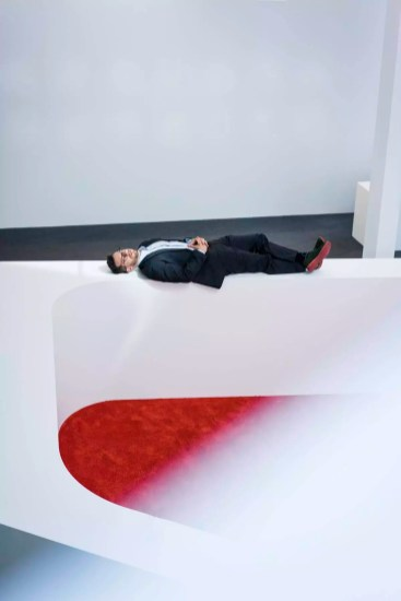 Businessman lying on reception desk in office