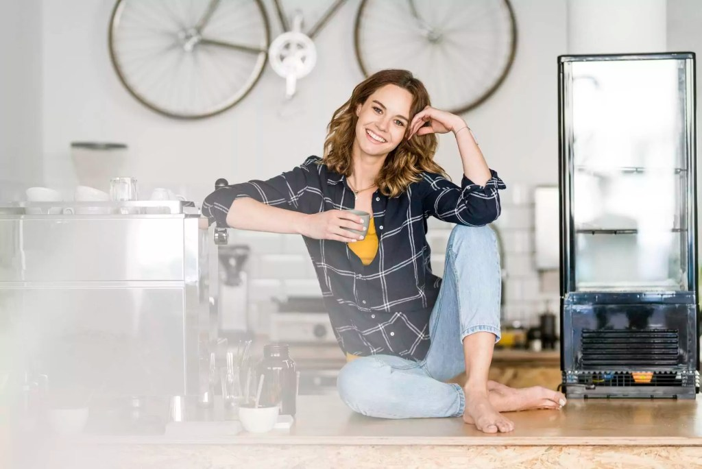 Young woman sitting barefoot on counter of her own coffee shop, drinking coffee - JOSF03438
