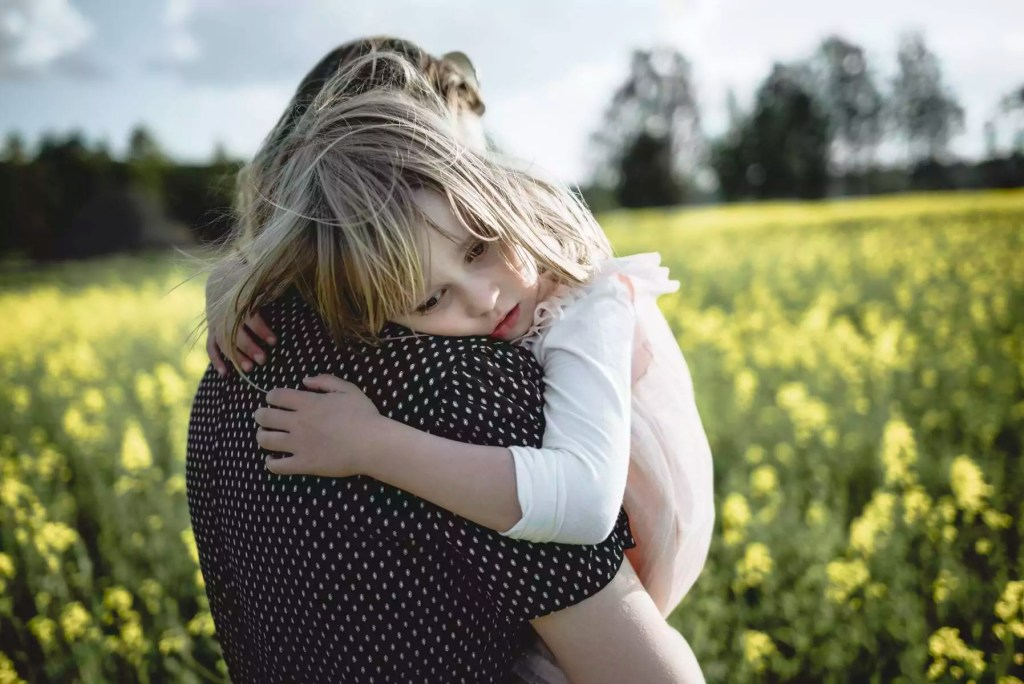 Portrait of little girl on her mother's arms in rape field - PSIF00008
