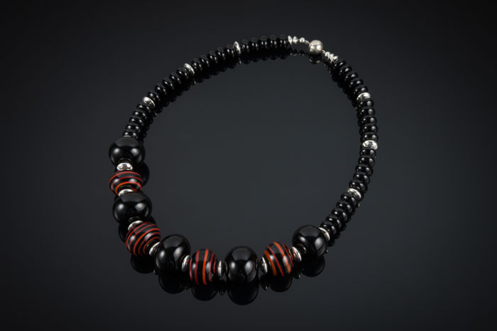 "Becky Congdon ""Embers Necklace"" 21.5"" handmade flameworked glass hollow striped and black beads with sterling silver accents and onyx gemstone $225. SOLD (photo by Ann Cady)"
