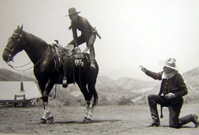 """William S. Hart coaches Johnny Mack Brown on how to do a crouper mount during the filming of """"Billy the Kid"""" ('30 MGM)."""