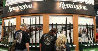 Attendees look at a display of Remington shotguns