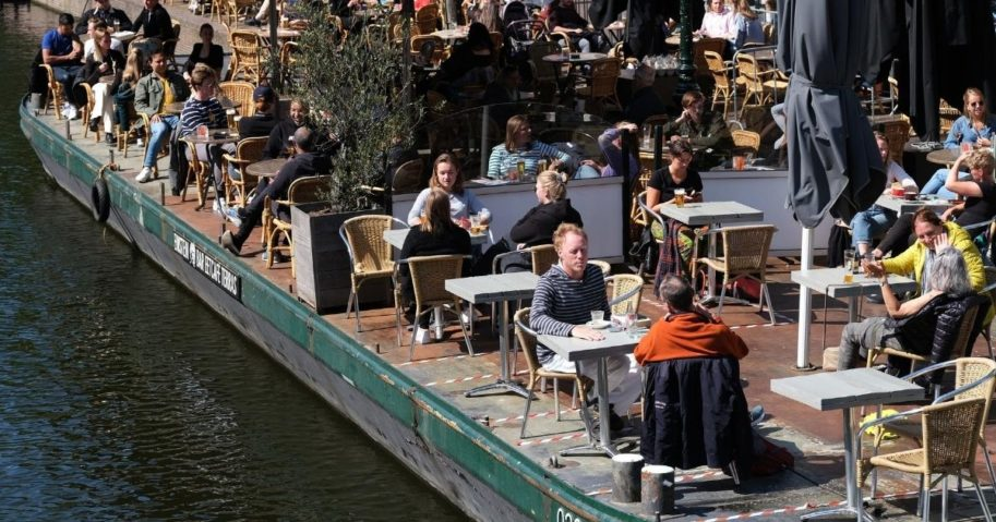 People eat and drink on an open terrace of a restaurant along a canal on June 9, 2020, in Leiden, Netherlands.