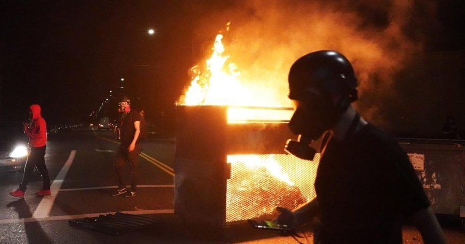 Demonstrators walk past a dumpster fire during another night of rioting in Portland, Oregon, on Aug. 14, 2020.