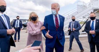 Jill Biden pulls the arm of her husband, Democratic presidential nominee Joe Biden, as he speaks to reporters before boarding his campaign plane at New Castle Airport in New Castle, Delaware, on Oct. 5, 2020, to travel to Miami.