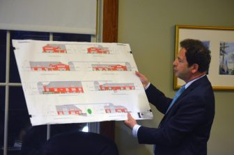 Domenic Sicari points at the proposed restaurant as it would have looked in its first iteration (left) and what is being proposed now (right)