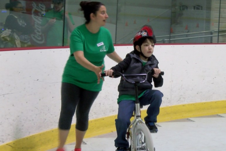 Michael Papapanayiotou gets help learning how to ride a bike at the iCanShine bike camp at Lawrence Academy in Groton
