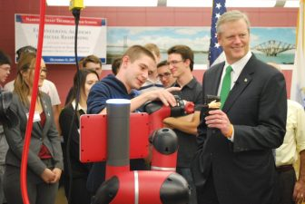 Drew Norton, a senior from Townsend, shows how a new robotic arm in Nashoba Tech's Engineering Academy can grab Gov. Charlie Baker's wallet during Baker's tour of the academy.