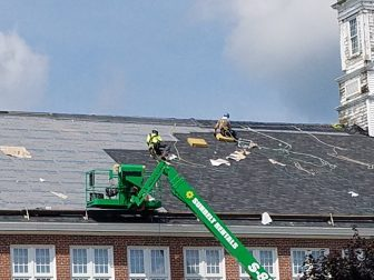 Workers replace the roof on the Abbot School. PHOTO BY JOYCE PELLINO CRANE