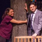 Actress Vivia Font hugs her beloved tree while her husband, played by Gabriel Marin, looks on in the laugh-out-loud comedy Native Gardens, playing at Merrimack Repertory Theatre through Oct. 7. The tree is a real oak – 18 feet tall and 2 tons of wood. PHOTO BY Meghan Moore