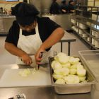 Mim Rahman, a Nashoba Tech postgraduate student from Westford, cuts onions for the salad.