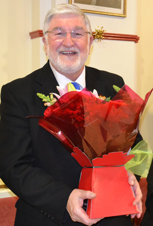 John Robson (left) receives a bouquet of flowers for his wife.