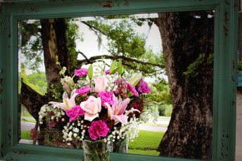 An acrylic cut vase of beautiful pink roses, larkspur, carnations, lilies and wax flower. A very feminine and frilly look to this bouquet. $60.00