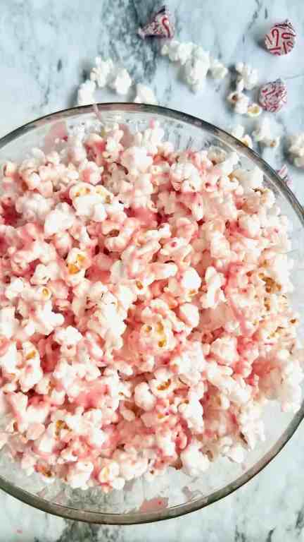 Make White Chocolate Peppermint Popcorn without the hassle of crushing candy canes. This easy Christmas treat is perfect for holiday movie nights. | We Three Shanes