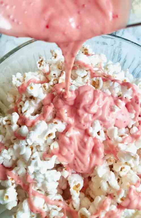 Melt candy cane Kisses with butter and pour all over popcorn to make the best Christmas movie treat! It's the easiest white chocolate peppermint popcorn recipe around! | We Three Shanes