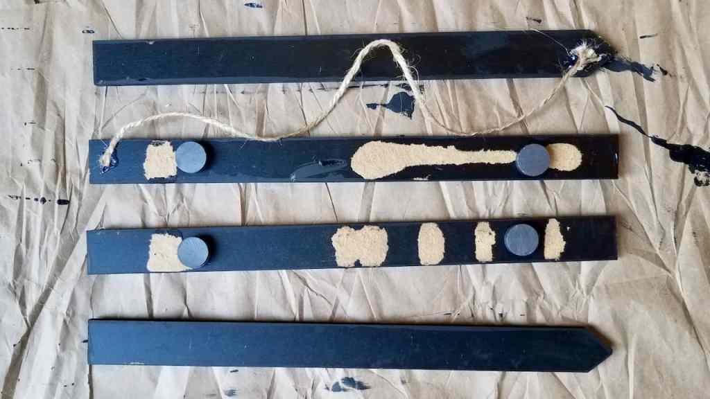 Showing how to glue the magnets and twine on dollar store sticks to make your own magnetic photo frame. | We Three Shanes