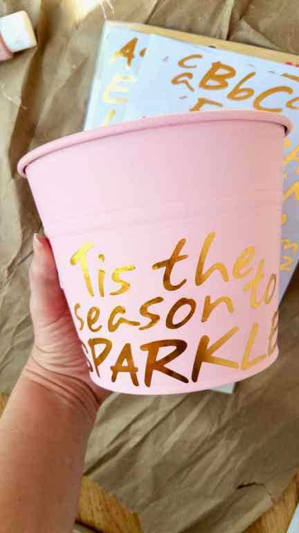 "Paint a dollar store bucket pink and use stickers to spell out ""Tis the season to sparkle"" for a girl's bedroom Christmas tree."