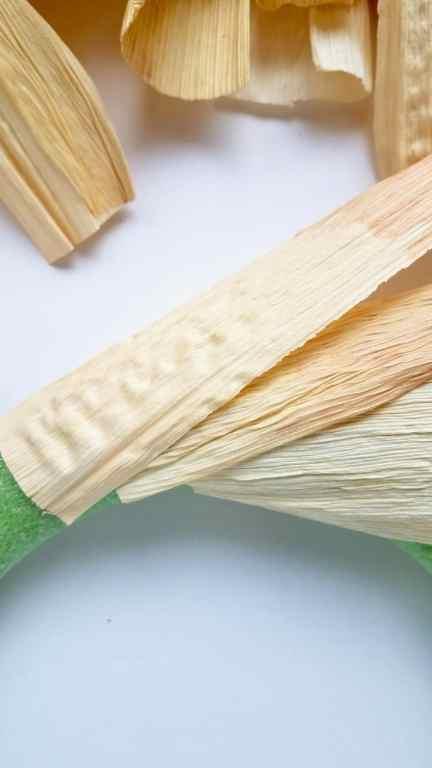 Use a hot glue gun to add corn husks to the foam wreath form when making a corn husk wreath.
