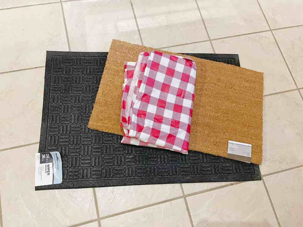 One black 24x36 inch doormat and a 18x30 inch brown mat are used to make a layered mat look for the front door. A red buffalo check table cloth is used to make the mat interchangeable.