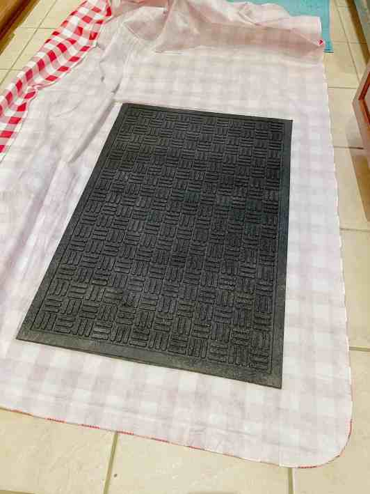 Lay your fabric face down on any clean surface and place the black mat face down on top of the table cloth fabric.