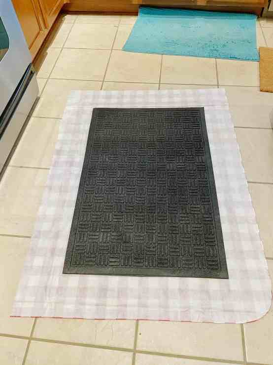 Cut out the fabric or table cloth with an excess of 6 inches around the black mat. You want enough extra fabric to wrap around your black mat.