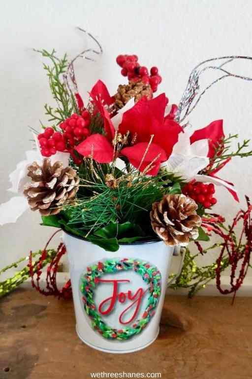 Learn how to make this cheerful Christmas Floral Arrangement using Dollar Tree supplies. An easy Christmas decor craft!   We Three Shanes
