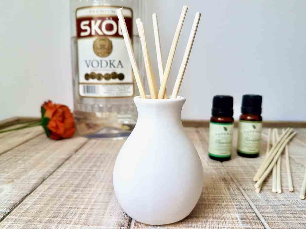 A cream colored bud vase, vodka, and essential oils are used to make a homemade reed diffuser.