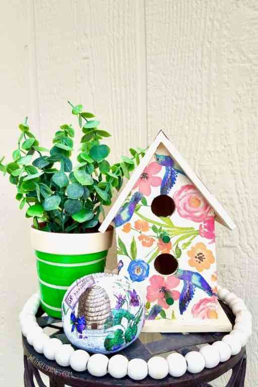 You can decoupage all kinds of things for spring and summer decor. A birdhouse decoupaged with flower napkins, a rock with a beehive and purple flowers, and a terra cotta pot with a green napkin with white stripes. | We Three Shanes
