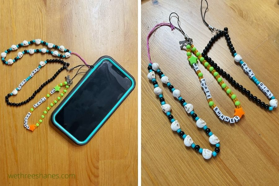 Three phone charms in different colors. One with blue, turquoise, and skull beads. Another with bright green and orange beads with t he words WE Three Shanes spelled out with letter beads. Another black and blue charm with the words baby girl.