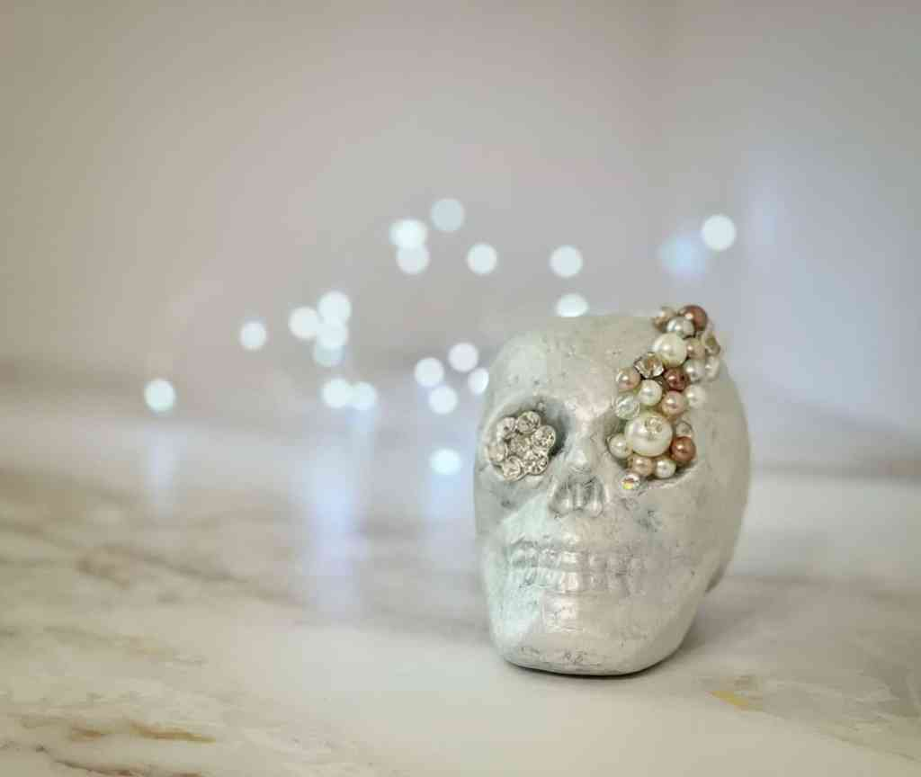 White foam skull head with pearls and bling glued to it.