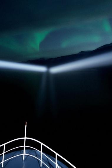 Les phares du bateau éclairent les aurores boréales