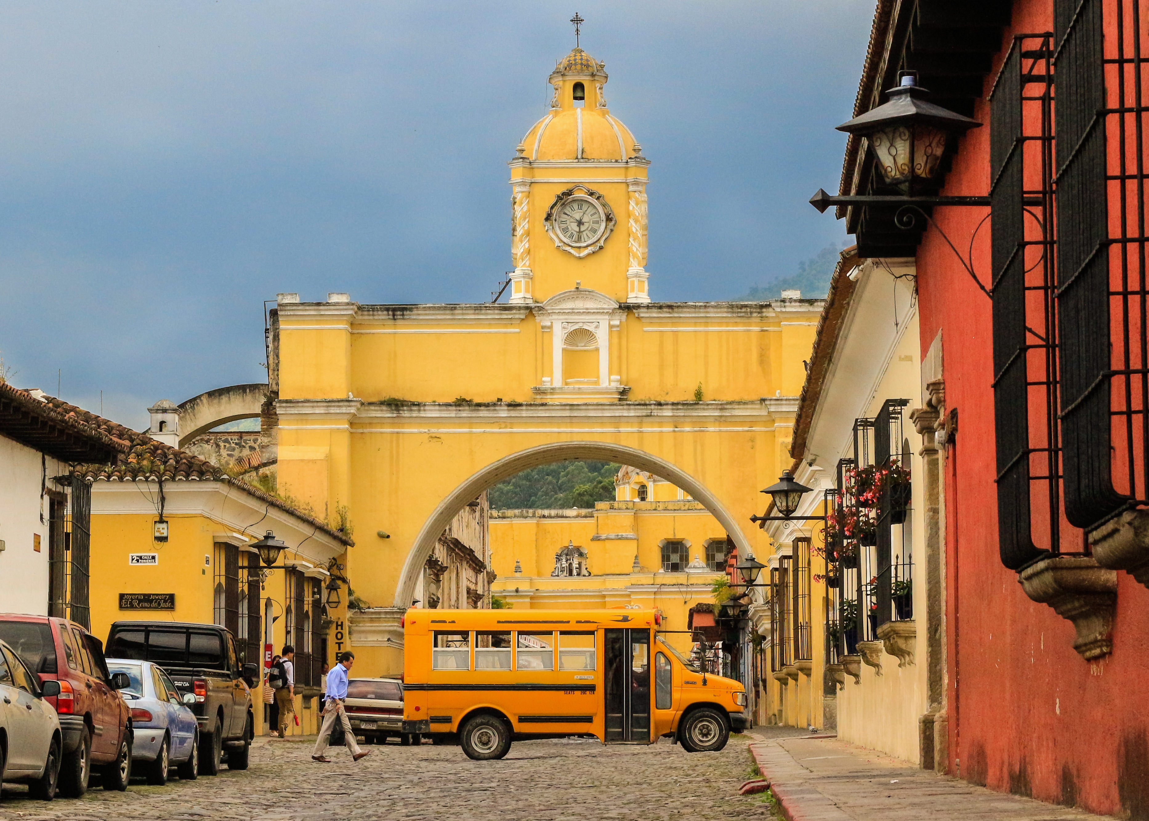 Streets of Antigua Guatemala with Arco de Santa Catalina arch and a yellow school bus.