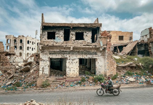 Man drives past building destroyed by conflict in Taz Yemen Feb 2020