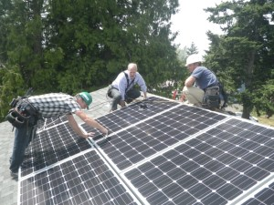 US Congressman Rick Larsen (center) helps complete installation of new panels on a KCLT home with Ecotech Installers John Wilkins (L) and Yonk Reinemer (R). Photo credit: Ecotech Solar.