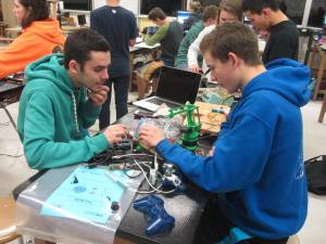 Senior Riley Allsop (L) and freshman Skyler Weight (R) program a robot for the regional competition.