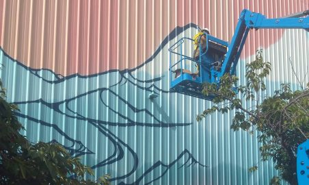 Gretchen is particularly concerned that the mural conveys motion and energy to break up the hard lines of the long wall and corrugation of the building. Photo courtesy: Nick Hartrich.