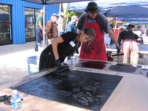 Volunteers inking a large plate